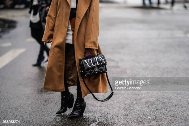 A guest wears a camel wrap coata black Valentino quilted bag black chunky heeled pointy toe booties outside Balmain during Paris Fashion Week...