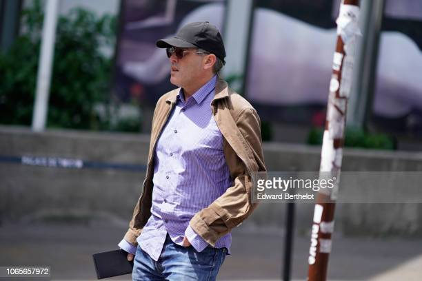 A guest wears a cap a beige jacket a purple shirt outside Rick Owens during Paris Fashion Week Menswear SpringSummer 2019 on June 21 2018 in Paris...