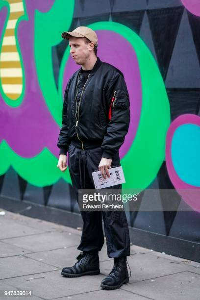 A guest wears a cap a black bomber jacket black pants during London Fashion Week Men's January 2018 at on January 6 2018 in London England