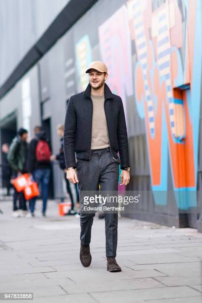 A guest wears a cap a black jacket black pants brown shoes during London Fashion Week Men's January 2018 at on January 6 2018 in London England