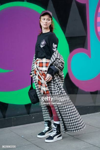 A guest wears a cap a black top a checked skirt a checked coat sneakers during London Fashion Week Men's January 2018 at on January 7 2018 in London...