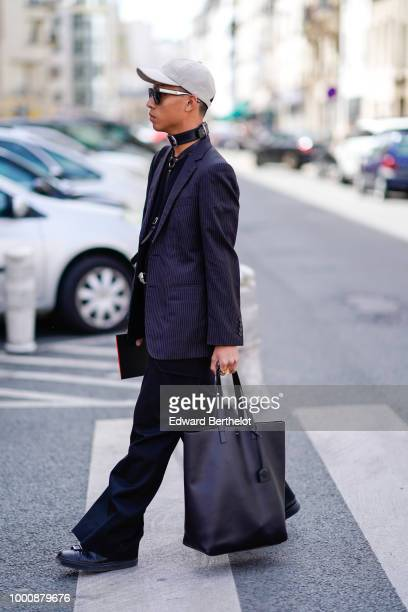 A guest wears a cap a blazer jacket a bag flared pants a choker outside Wooyoungmi during Paris Fashion Week Menswear SpringSummer 2019 on June 23...