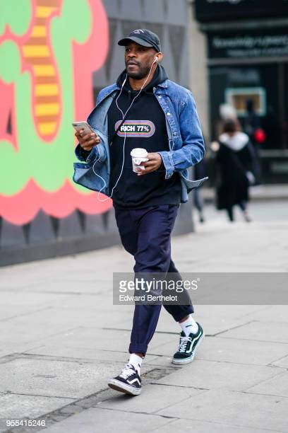 A guest wears a cap a blue denim jacket a hoodie sweater blue pants sneakers during London Fashion Week Men's January 2018 at on January 6 2018 in...