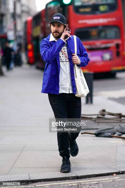 A guest wears a cap a blue jacket black pants blacks hoes a white shirt during London Fashion Week Men's January 2018 at on January 6 2018 in London...