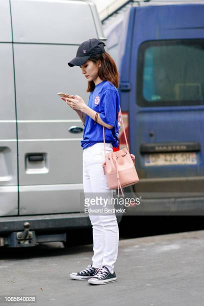 A guest wears a cap a blue top white pants a pink bag sneakers shoes outside Issey Miyake during Paris Fashion Week Menswear SpringSummer 2019 on...