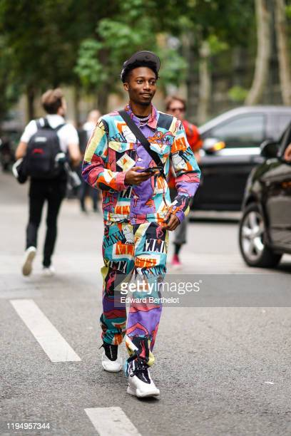 Guest wears a cap, a chain necklace, a colorful Patta jacket, matched full length pants, black and white Alexander Wang sneakers, outside Off-White,...