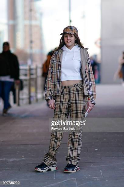 A guest wears a cap a checked jacket a bare belly white hoodie sweater pants sneakers during London Fashion Week February 2018 on February 17 2018 in...