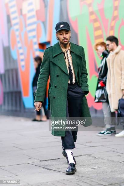 A guest wears a cap a green coat black pants during London Fashion Week Men's January 2018 at on January 6 2018 in London England
