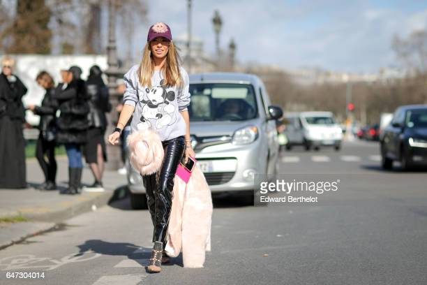 A guest wears a cap a Mickey Mouse top black vinyl pants outside the Manish Arora show during Paris Fashion Week Womenswear Fall/Winter 2017/2018 on...