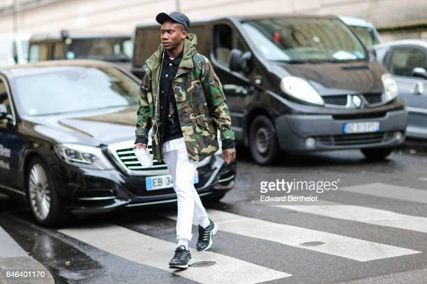 A guest wears a cap a military camouflage print coat white pants and sneakers shoes outside the JOUR/NE show during Paris Fashion Week Womenswear...