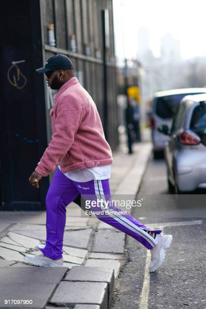 A guest wears a cap a pink jacket purple sportswear pants shoes during London Fashion Week Men's January 2018 at on January 6 2018 in London England