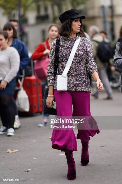 A guest wears a cap a pull over a white bag purple cropped flare large pants purple suede shoes outside Valentin Yudashkin during Paris Fashion Week...