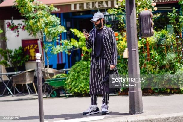 A guest wears a cap a striped jacket striped pants sneakers shoes outside Wooyoungmi during Paris Fashion Week Menswear SpringSummer 2019 on June 23...