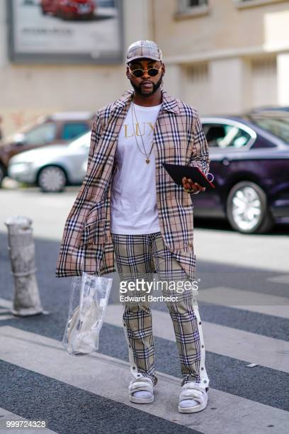 A guest wears a cap a tartan checked blazer jacket a white tshirt with the word 'LUX' printed tartan checked pants white socks sandals outside...