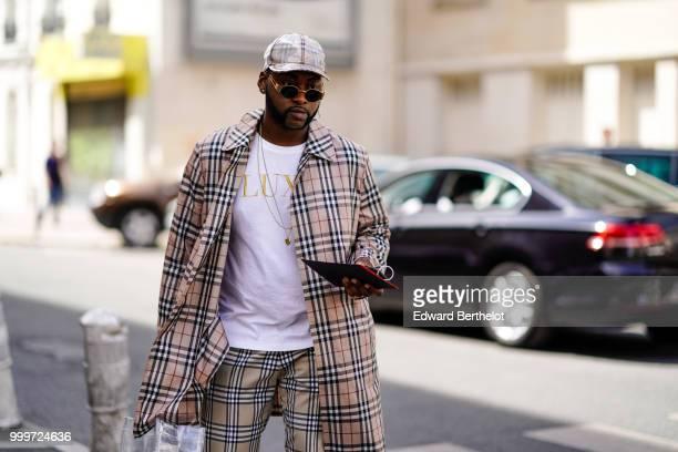 A guest wears a cap a tartan checked jacket outside Wooyoungmi during Paris Fashion Week Menswear SpringSummer 2019 on June 23 2018 in Paris France