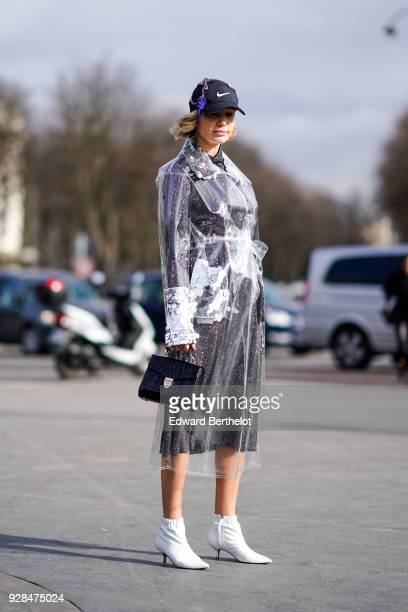 A guest wears a cap a transparent plastic jacket a dress a bag white shoes outside Chanel during Paris Fashion Week Womenswear Fall/Winter 2018/2019...