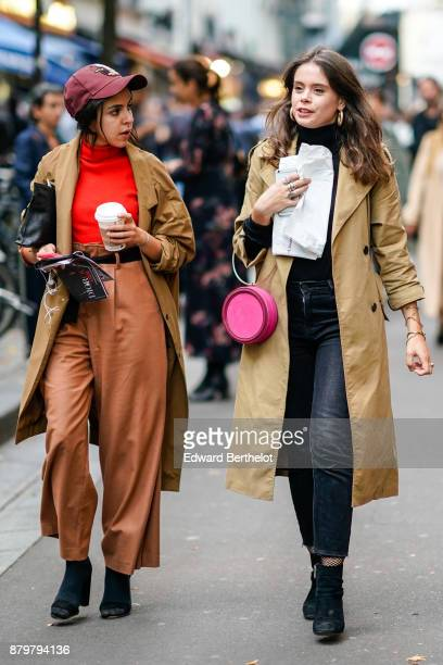 A guest wears a cap an orange turtleneck top a brown coat brown flare cropped pants black shoes holds a starbucks coffee cup a guest wears a beige...