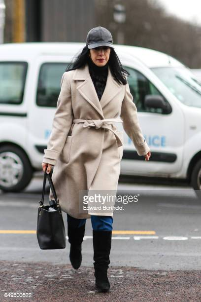 Guest wears a cap, and a beige trench coat, outside the Chanel show, during Paris Fashion Week Womenswear Fall/Winter 2017/2018, on March 7, 2017 in...