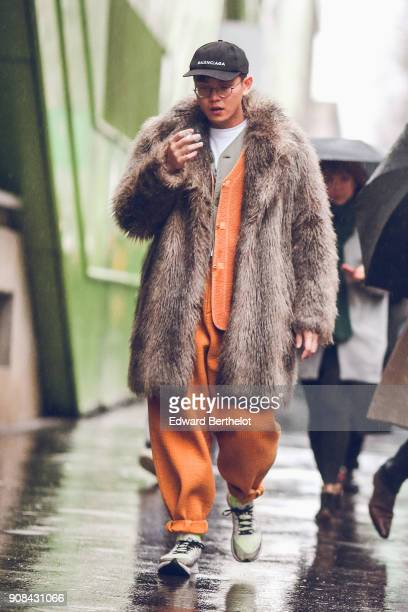 A guest wears a cap glasses a fur coat an orange outfit under the rain outside Paul Smith during Paris Fashion Week Menswear Fall Winter 20182019 on...