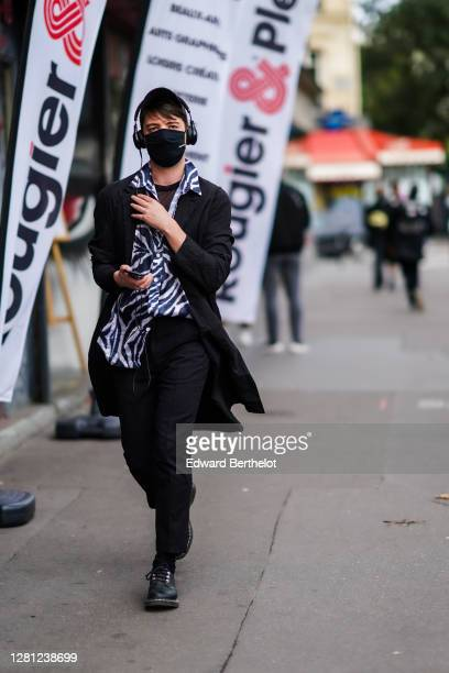 A guest wears a cap hat JBL headphones a black face mask with printed Stay Safe a black coat a blue and white zebra print shirt black pants leather...