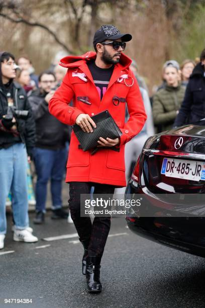 A guest wears a cap sunglasses a red coat black pants black leather shoes a clutch outside Dior during Paris Fashion Week Menswear Fall Winter...