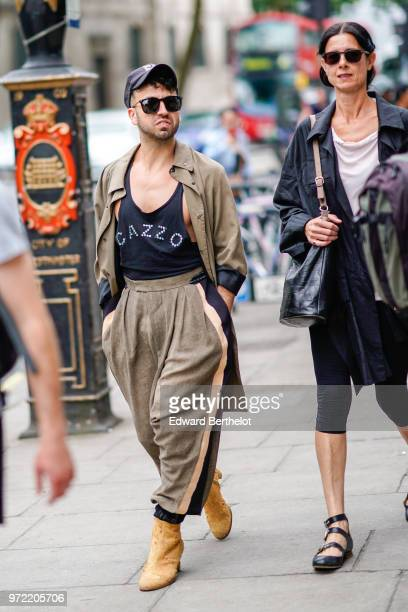 A guest wears a cap sunglasses a trench coat a tank top with printed CAZZO during London Fashion Week Men's June 2018 on June 09 2018 in London...