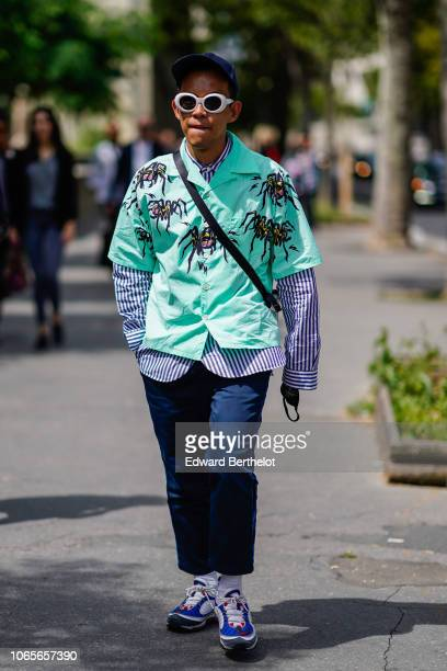 A guest wears a cap white sunglasses a blue turquoise shirt over a striped shirt with long sleeves blue pants sneakers outside Rick Owens during...
