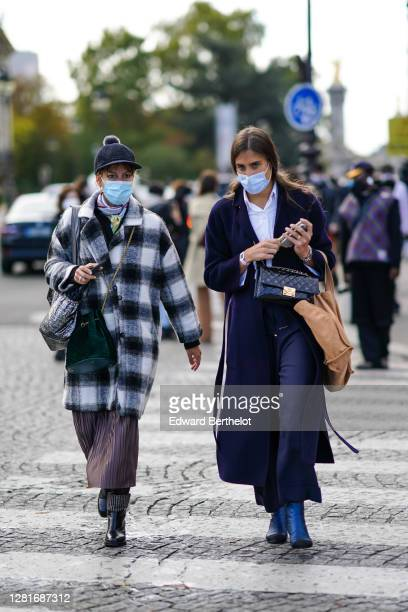 Guest wears a cap with a pompom, a black and white checked long coat, a scarf ; a guest wears a white shirt, a black leather quilted bag, navy blue...