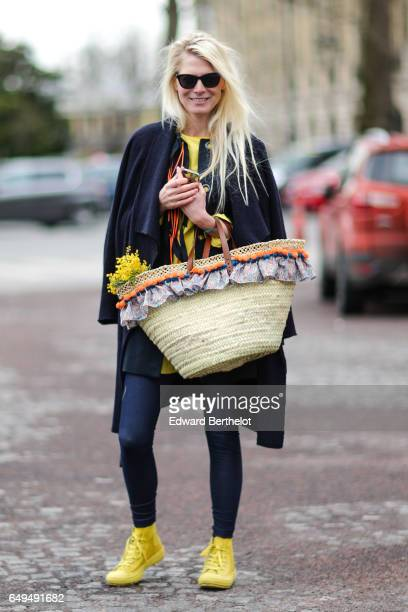 A guest wears a cape a basket yellow shoes outside the Chanel show during Paris Fashion Week Womenswear Fall/Winter 2017/2018 on March 7 2017 in...