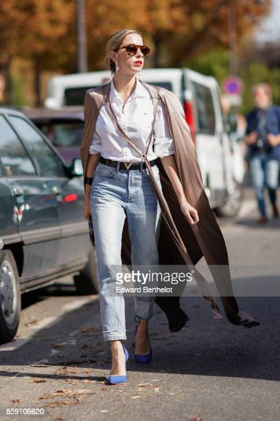 A guest wears a cape a white shirt cropped jeans blue heels outside Issey Miyake during Paris Fashion Week Womenswear Spring/Summer 2018 on September...
