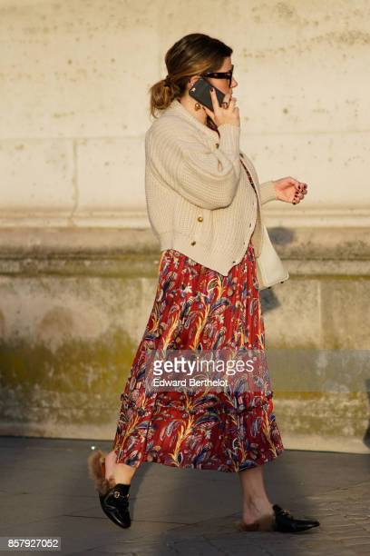 A guest wears a cardigan a red flower print skirt black leather shoes with brown fur outside Louis Vuitton during Paris Fashion Week Womenswear...