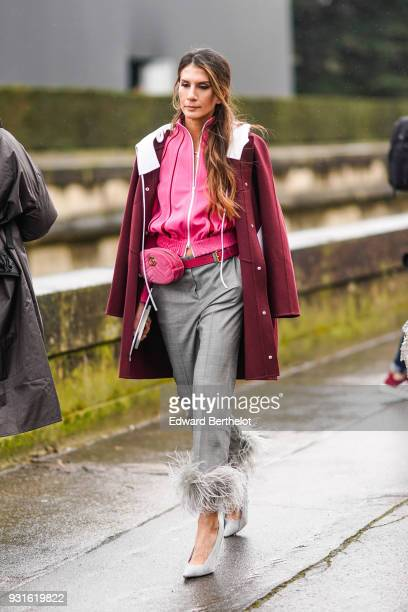 A guest wears a carmine red coat with a white collar a pink jacket a pink belt bag light grey pants with hems adorned with feathers light grey pumps...