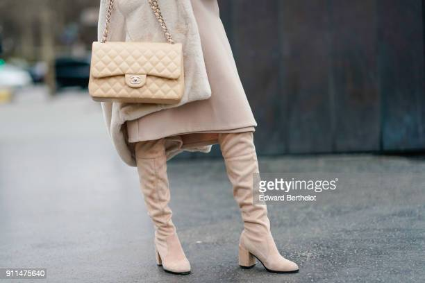 A guest wears a Chanel bag and boots outside Chanel during Paris Fashion Week Haute Couture Spring/Summer 2018 on January 23 2018 in Paris France