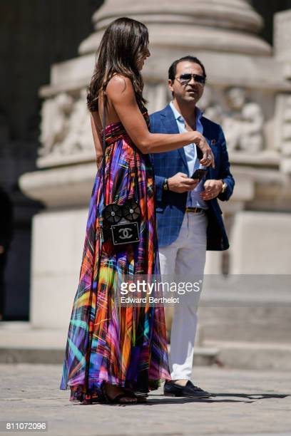 A guest wears a Chanel black bag shaped as a traditional film camera and a multicolor ruffle dress outside the Chanel show during Paris Fashion Week...