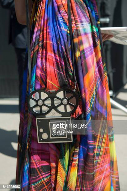 A guest wears a Chanel dress with a Chanel film camera bag day 3 of Paris Haute Couture Fashion Week Autumn/Winter 2017 on July 4 2017 in Paris France