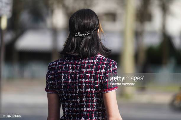 Guest wears a Chanel hair brooch, a checked purple and red tweed jacket, outside Chanel, during Paris Fashion Week - Womenswear Fall/Winter 2020/2021...