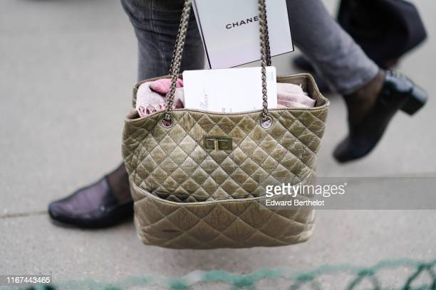A guest wears a Chanel khaki bag outside the Chanel Cruise Collection 2020 At Grand Palais on May 03 2019 in Paris France