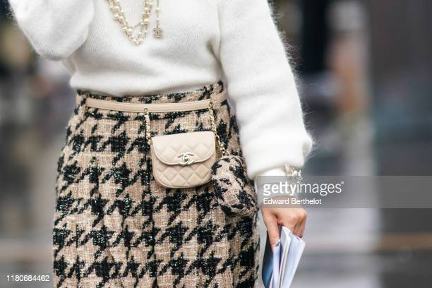 Guest wears a Chanel necklace, a bangle, a white fluffy hi-neck sweater, beige and black houndstooth pants, a beige Chanel belt-bag with a beige and...