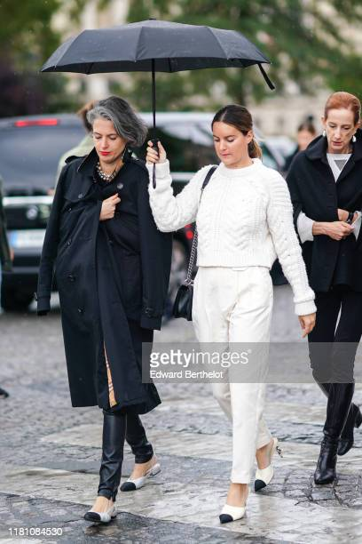 Guest wears a Chanel necklace, a black Burberry trench coat, black leather pants, black and white slingback Chanel flat shoes ; A guest wears a white...
