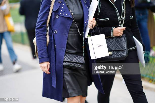 A guest wears a Chanel necklace a black leather dress a blue trench coat with studded collar and lapels a black Chanel bag outside the Chanel Cruise...