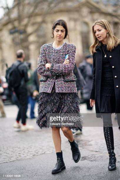 Guest wears a Chanel pink, grey and black tweed suit with a fur-like skirt, black boots ; a guest wears a ruffled black dress, a black coat,...
