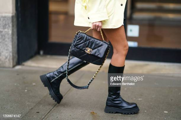 Guest wears a Chanel quilted bag with a golden logo, black leather boots, during New York Fashion Week Fall Winter 2020, on February 11, 2020 in New...