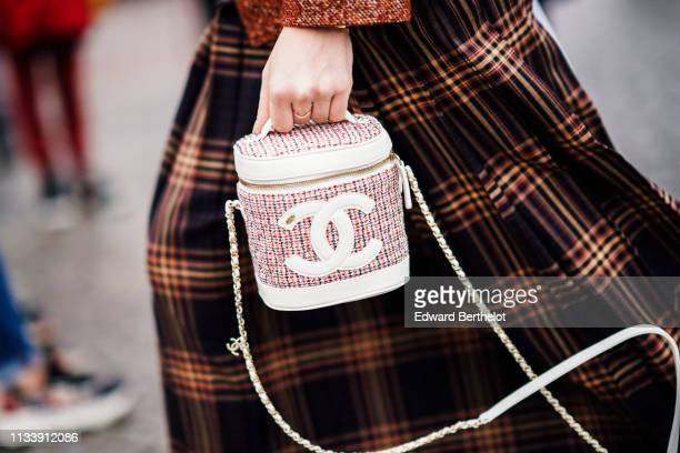 Guest wears a Chanel rust-color tweed jacket, a black and brown tartan pleated skirt, a Chanel red, black and white tweed bag, outside Chanel, during...
