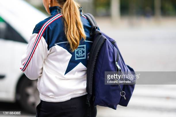 Guest wears a Chanel sport jacket with stripes and printed logo, a purple backpack, outside Chanel, during Paris Fashion Week - Womenswear Spring...