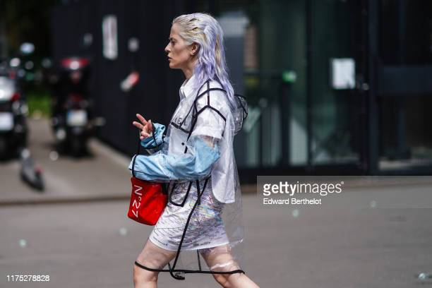 A guest wears a Chanel white shirt a mini skirt with the Parisian subway map pattern a red bag a transparent vinyl hooded black trimmed coat outside...