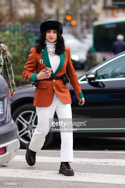Guest wears a chapka, earrings, rings, a colorful necklace, a white turtleneck, a rust-color jacket with green lapels and brass buttons, a leopard...