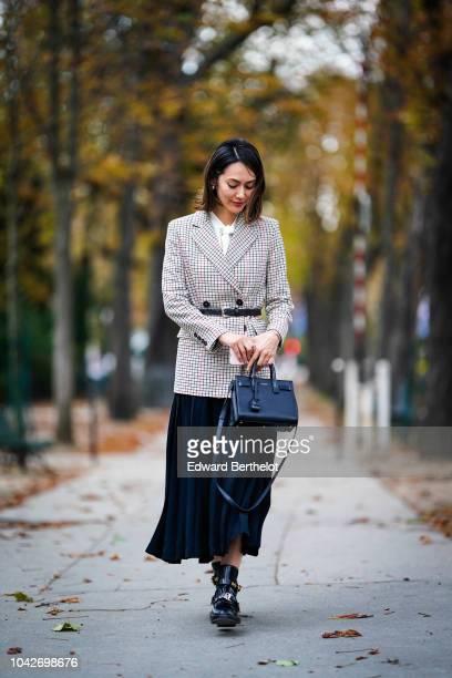 A guest wears a checked blazer jacket a black pleated skirt a Saint Laurent Sac de Jour bag outside Yohji Yamamoto during Paris Fashion Week...