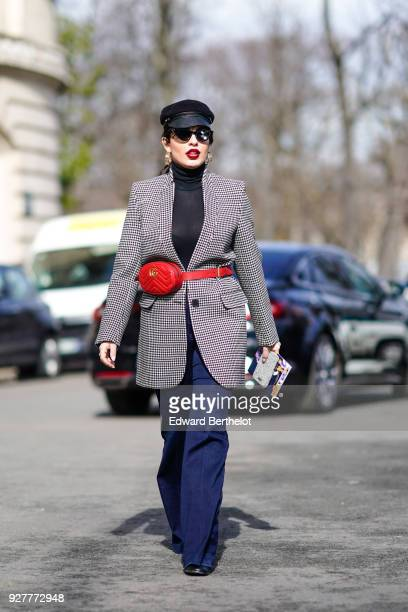 A guest wears a checked blazer jacket and a red Gucci belt bag during Paris Fashion Week Womenswear Fall/Winter 2018/2019 on March 5 2018 in Paris...