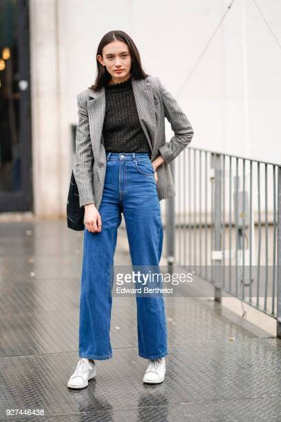 A guest wears a checked blazer jacket blue flare jeans white sneakers during Paris Fashion Week Womenswear Fall/Winter 2018/2019 on March 4 2018 in...