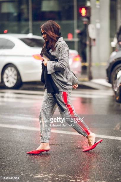 A guest wears a checked blazer jacket pants with red printed stripes red shoes under the rain outside Paul Smith during Paris Fashion Week Menswear...